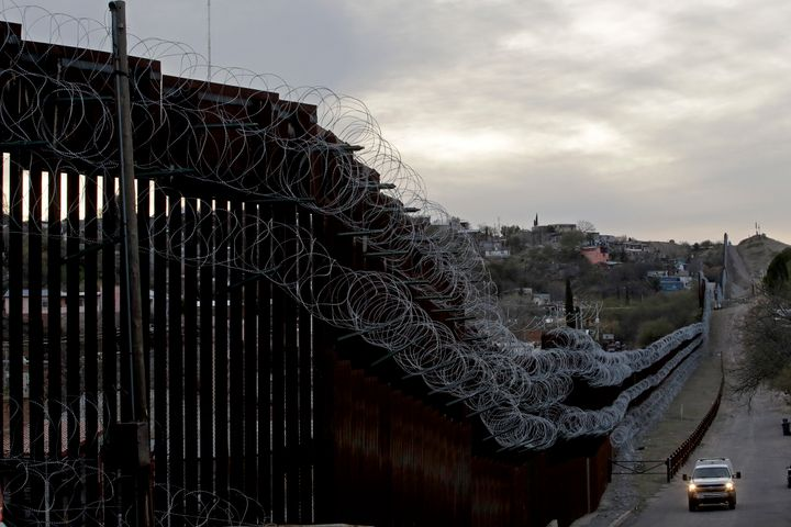 A U.S. Customs and Border Protection agent patrols on the U.S. side of a razor-wire-covered border barrier that separates Nog