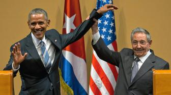 FILE - In this March 21, 2016 file photo, Cuban President Raul Castro, right, lifts up the arm of President Barack Obama at the conclusion of their joint news conference at the Palace of the Revolution, in Havana, Cuba. Donald Trump's pledge to undo Obama's detente with Cuba is provoking widespread anxiety among ordinary Cubans, who were paying little attention to the U.S. presidential campaign until now. (AP Photo/Ramon Espinosa, File)