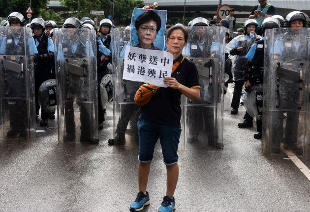 A protester holds a placard against Chief Executive of Hong Kong Carrie Lam during the demonstration...