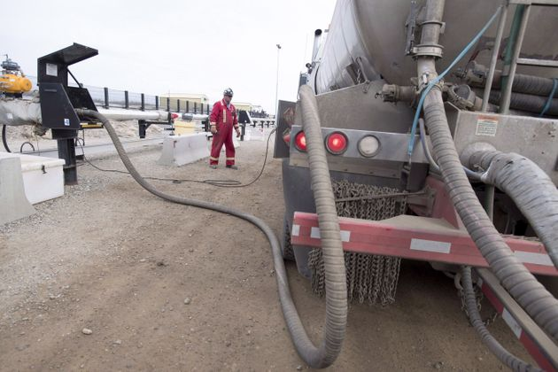 A worker fills his truck at the Shell Sunset water hub for the Groundbirch Saturn natural gas plant outside...