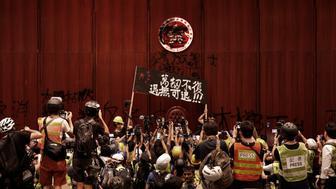 """Manifestantes levantan un cartel que lee parcialmente, """"No nos rendiremos"""" enfrente de un símbolo vandalizado de Hong Kong, tras entrar a la Cámara Legislativa para protestar por una medida de extradición en Hong Kong, el lunes 1 de julio del 2019. (AP Foto/Vincent Yu)"""