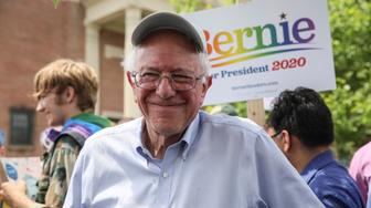 Democratic presidential candidate Sen. Bernie Sanders, I-Vt., smiles as he stands in the shade before marching with supporters in the Nashua Pride Parade in Nashua, N.H. Saturday, June 29, 2019: (AP Photo/ Cheryl Senter)