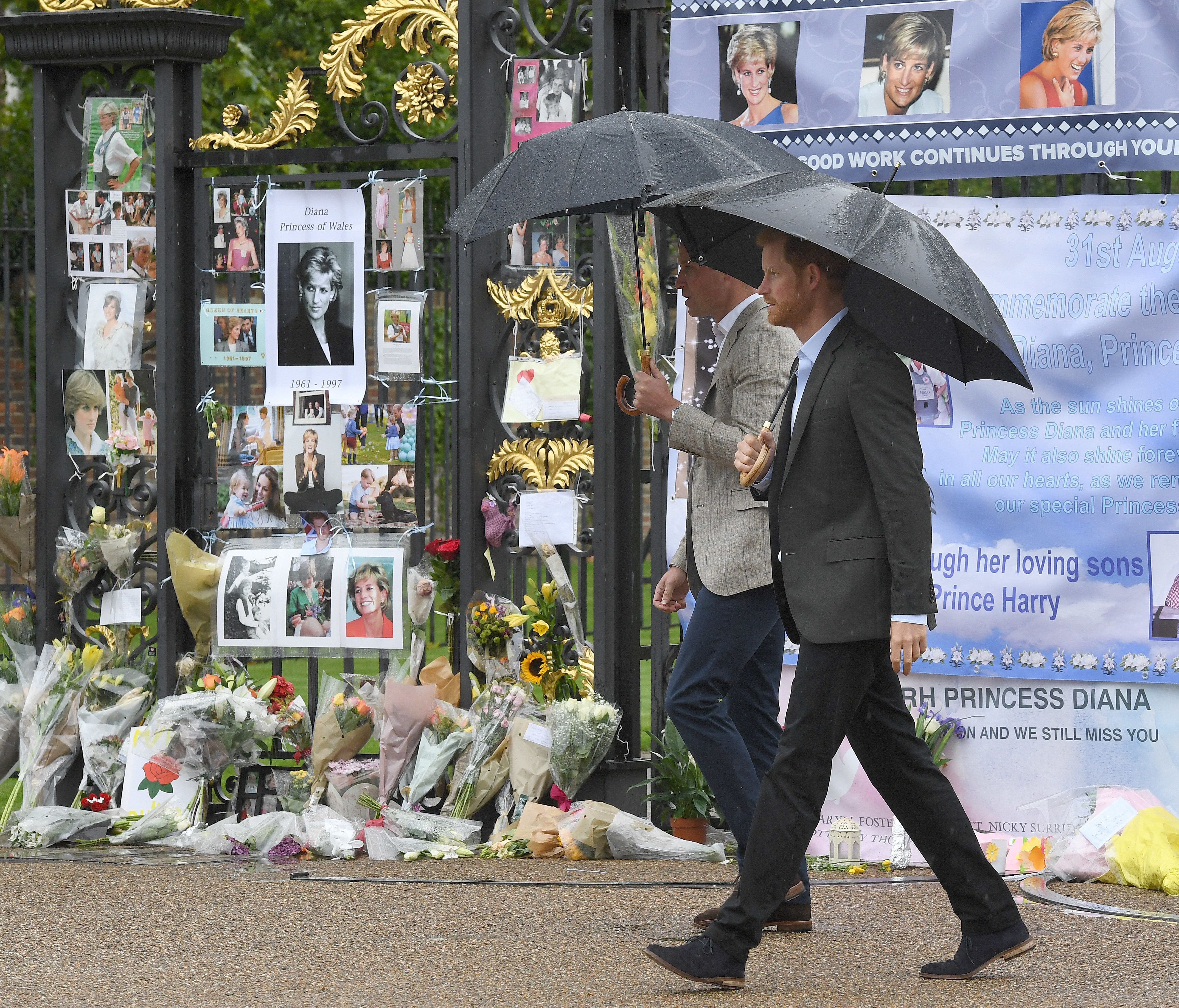 William and Harry look at tributes left by the public dedicated to their mother Princess Diana following their visit The White Garden, dedicated to the memory of Princess Diana, in Kensington Palace on Aug. 30, 2017.