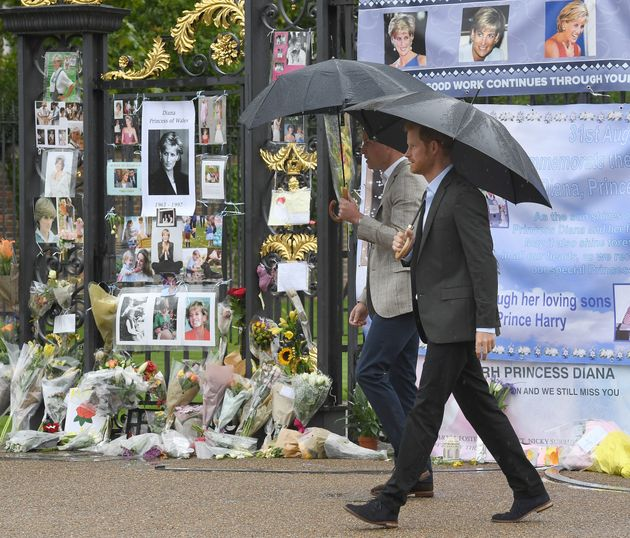 William and Harry look at tributes left by the public dedicated to their mother Princess Diana following...