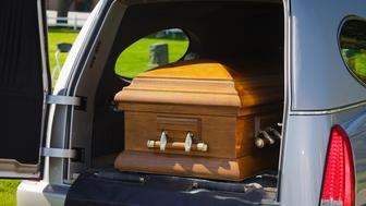 A casket in the back of an open hearse.