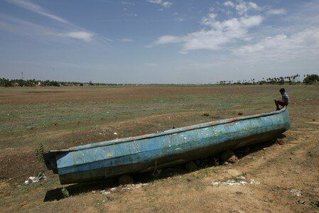 A man sits on a fishing boat stranded on the bed of the dried-up lake in Thiruninravur, June 29,