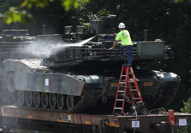 A worker washes one of two M1A1 Abrams tanks that are loaded on rail cars July 2 in Washington,
