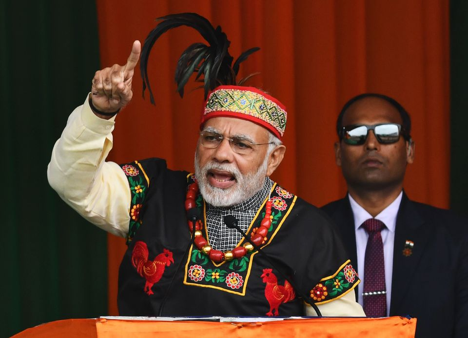 Prime Minister Narendra Modi gestures while addressing a Bharatiya Janata Party rally, dressed in traditional...