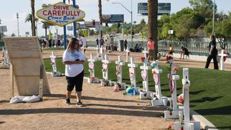 LAS VEGAS, NEVADA - OCTOBER 01:  Visitors look at crosses set up for shooting victims behind the Welcome to Fabulous Las Vegas sign on October 1, 2018 in Las Vegas, Nevada. Retired carpenter Greg Zanis, who installed 58 crosses last year - one for each of the victims of the shooting - set up the memorial again with new crosses for the anniversary of the massacre. On October 1, 2017, Stephen Paddock opened fire on the Route 91 Harvest country music festival in Las Vegas killing 58 people and injuring more than 800 in the deadliest mass shooting event in U.S. history.  (Photo by Ethan Miller/Getty Images)