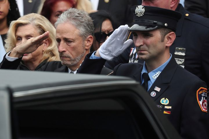 Comedian Jon Stewart salutes the casket of former NYPD detective Luis Alvarez during a funerary procession on Wednesday.