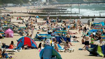 People enjoy the sunshine on the beach in Bournemouth, Dorset, England, as temperatures are set to rise over the weekend, Friday June 28, 2019. (Steve Parsons/PA via AP)