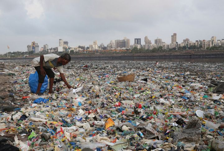 A man collects plastic and other recyclable material from the shores of the Arabian Sea, littered with plastic bags and other
