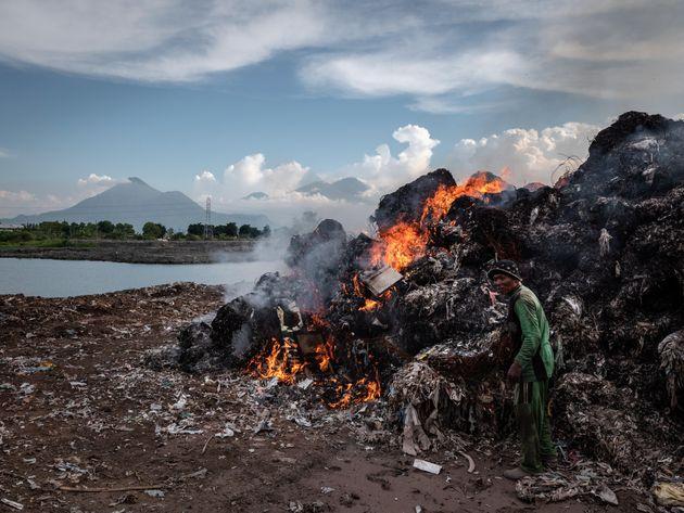A man burns plastic waste at a import plastic waste dump in Mojokerto on Dec. 4, 2018, in Mojokerto,...