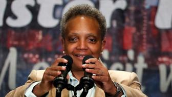 Chicago Mayor Lori Lightfoot adjusts the microphones as she addresses the Rainbow PUSH Coalition Annual International Convention, before former Democratic presidential candidate Vice President Joe Biden's address Friday, June 28, 2019, in Chicago. (AP Photo/Charles Rex Arbogast)