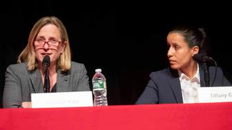 FILE - In this Thursday, June 13, 2019, file photo, public defender Tiffany Caban, right, listens as Queens Borough President Melinda Katz speaks during a Queens District Attorney candidates' forum at St. John's University in New York. The campaign between the two has become a test between left-wing and moderate Democrats. (AP Photo/Mary Altaffer, File)