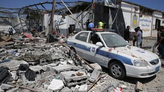 Debris covers the ground and an emergency vehicle after an airstrike at a detention center in Tajoura, east of Tripoli in Libya, Wednesday, July 3, 2019. An airstrike hit the detention center for migrants early Wednesday, killing several.   (AP Photo/Hazem Ahmed)