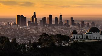 Aerial view of the downtown Los Angeles skyline and the Griffith Park Observatory just after sunrise during the golden hour