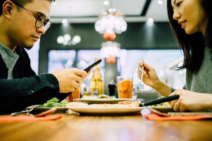 携帯に見入る男性と、不満そうな女性(イメージ写真)