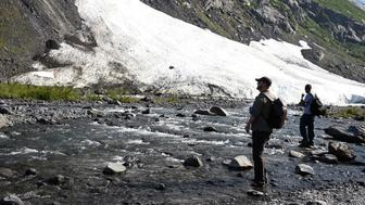 GIRDWOOD, AK - JULY 04: Sam Lightle, left, from Anchorage, and Brandon York from Jacksonville, Florida, take in the scenery along a creek below the Byron Glacier on July 4, 2019 near Portage Lake in Girdwood, Alaska. Alaska is bracing for record warm temperatures and dry conditions in parts of the state. (Photo by Lance King/Getty Images)