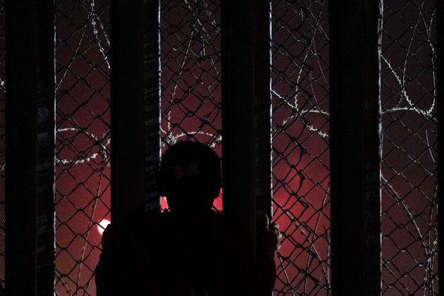 Una niña migrante en la valla fronteriza entre Estados unidos y