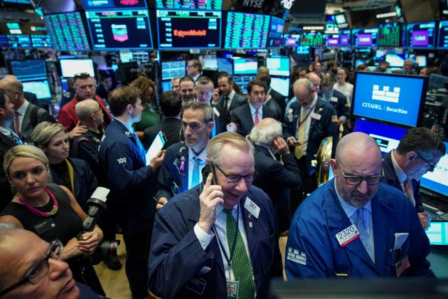 Traders gather around a post as they wait for the start of the trading day at the New York Stock Exchange,...