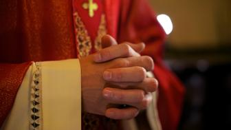 Catholic priest on altar praying with hands joined during mass service in church
