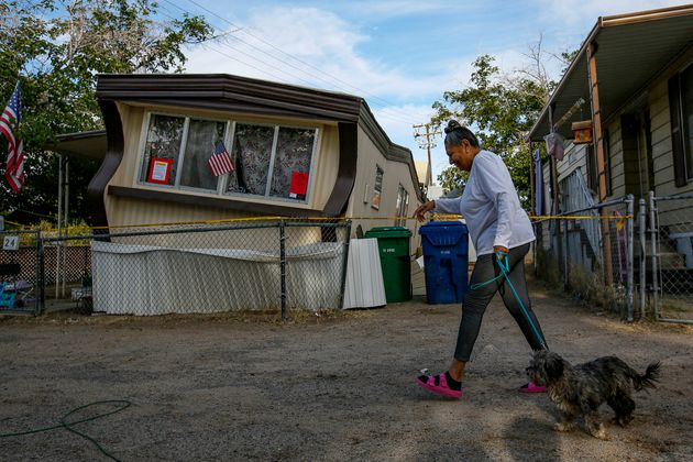 Carmen Rivera, 65, on morning walk with her dog Ash passes by a mobile home dislodged in Torusdale Estates...