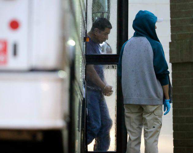 Immigrants in handcuffs and ankle chains arrive at the Federal Courthouse in McAllen, Texas, for hearings...
