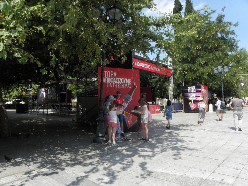 Unos turistas paran ante la publicidad de Syriza en la plaza de