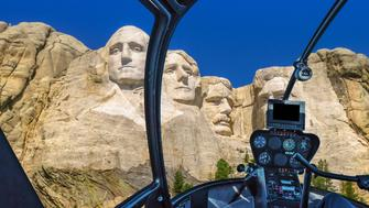 Helicopter interior flying on Mount Rushmore National Memorial of United States of America in South Dakota. US historical presidents: Washington, Jefferson, Roosevelt, Lincoln. NP scenic flight.