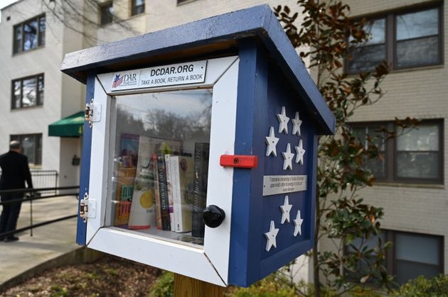 A Little Free Library, which inspired the Little Free Pantry project, in front of an apartment building...