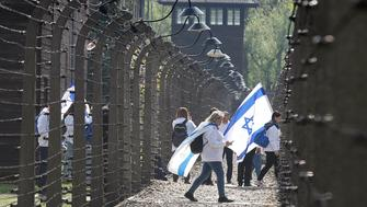Participants in the Jewish event of Holocaust remembrance walk in the former Nazi German World War II death camp of Auschwitz shortly before the start of the annual March of the Living in which young Jews from around the world walk from Auschwitz to Birkenau in memory of the 6 million Holocaust victims, in Oswiecim, Poland, Thursday, May 2, 2019. (AP Photo/Czarek Sokolowski)