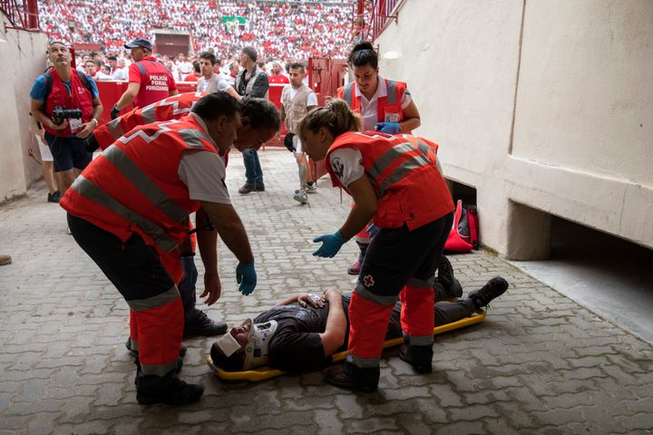 Paramedics prepare to take unidentified man to the hospital after the running of the bulls.
