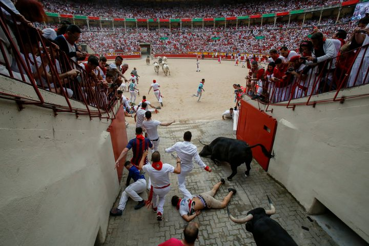 An unidentified runner appears to lie unconscious near the bullring as other runners and bulls trample him.