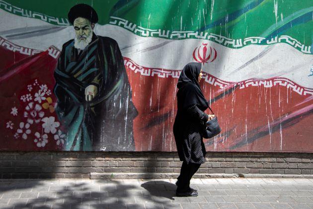 한 여성이 이란 혁명을 이끌었던 최고지도자 아야톨라 루홀라 호메이니(1902-1989) 벽화 앞을 걸어가고 있다. 테헤란, 이란. 2019년