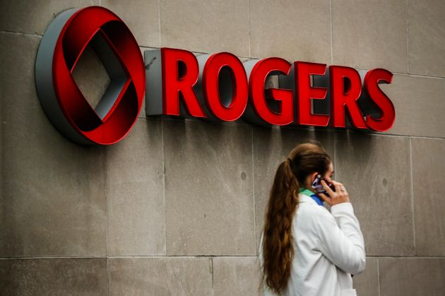 A woman speaks on her phone in front of a Rogers sign in Toronto on April 22,