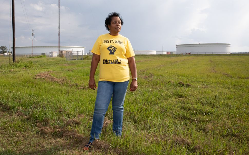 Sharon Lavinge founder of RISE St. James in font of oil storage tanks in St. James
