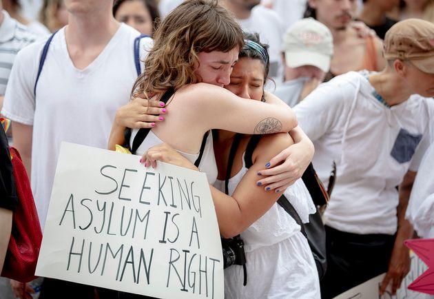 Karla Arias, a la derecha, reconforta a su amiga, Katie Drackert, durante un minuto de silencio por los...