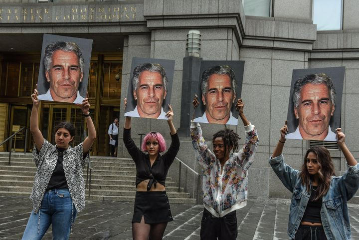 "Members of a protest group called ""Hot Mess"" hold up signs of Jeffrey Epstein in front of the federal courthouse on July 8, 2"