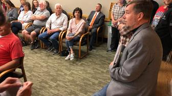 Sen. Brian Boquist, right, waits prior to a hearing at the state capital in Salem, Ore. on Monday, July 8, 2019. A special committee of the Oregon state Senate is holding a hearing over the lawmaker's comments he made during a Republican revolt over climate legislation. (AP Photo/Andrew Selsky)