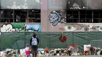 FILE - In this Dec. 13, 2016, file photo, flowers, pictures, signs and candles, are placed at the scene of a warehouse fire in Oakland, Calif. Two men have pleaded not guilty to involuntary manslaughter charges in connection with a fire in an illegally converted Northern California warehouse that killed 36 people. Derick Almena and Max Harris entered pleas to 36 counts of involuntary manslaughter each, Tuesday, Sept. 26, 2017. (AP Photo/Marcio Jose Sanchez, File)