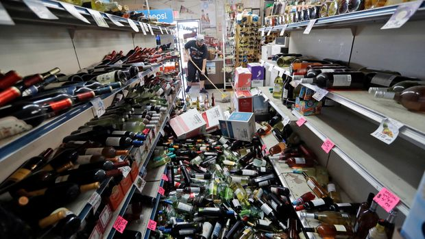 Bottles of wine are strewn in the middle of an aisle as Victor Abdullatif, background center, mops inside of the Eastridge Market, his family's store, Saturday, July 6, 2019, in Ridgecrest, Calif. Crews in Southern California assessed damage to cracked and burned buildings, broken roads, leaking water and gas lines and other infrastructure Saturday after the largest earthquake the region has seen in nearly 20 years jolted an area from Sacramento to Las Vegas to Mexico. (AP Photo/Marcio Jose Sanchez)