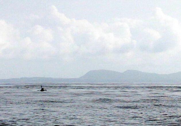 与那国島の間近まで迫った丸木舟(9日、伴走船より撮影、「3万年前の航海 徹底再現プロジェクト」提供)