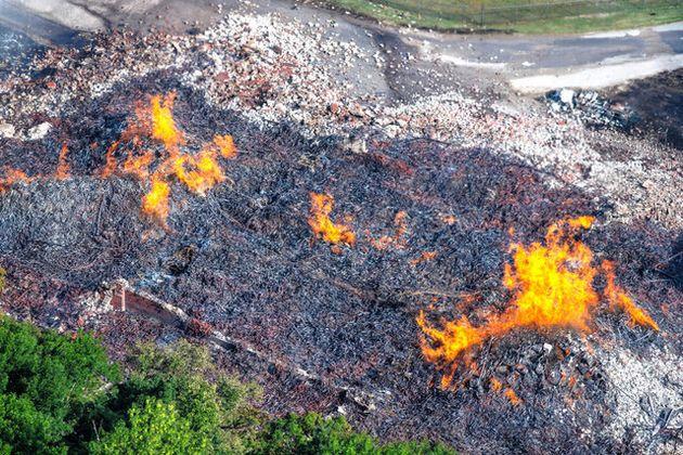 米ケンタッキー州で3日、ジムビームの蒸留所にある倉庫から燃え立つ炎。火災の影響で大量のウイスキーが近くの川に流れた(AP)