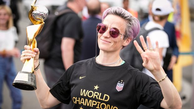 NEWARK, NJ - JULY 08: Megan Rapinoe #15 of United States with pink dyed hair holds up four fingers indicating four World Cup Championships wearing a shirt that says World Champions 2019 and holding the FIFA Women's World Cup Trophy as the USA Women's National team arrives back in the U.S. after winning their 4th FIFA World Cup title  against Netherlands at Newark Liberty International Airport on July 08, 2019 in Newark, NJ, USA. (Photo by Ira L. Black/Corbis via Getty Images)