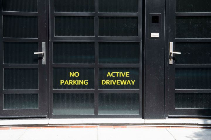 "Signs on the back entrance to Noam Gottesman's complex read ""No Parking"" and ""Active Driveway."""