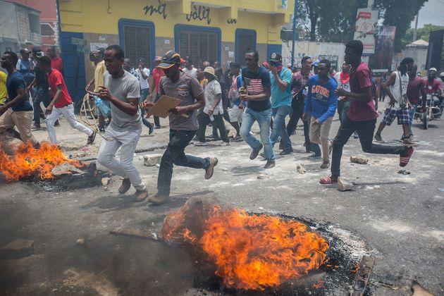 아이티 시위자들이 6월 9일 포르토프랭스에서 조베넬 모이즈(Jovenel Moïse) 대통령 퇴진을 요구하는 시위 중 불에 타고 있는 타이어 옆을 뛰어가고 있다.