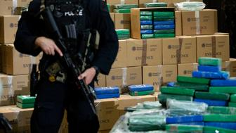 FILE - In this Friday, June 21, 2019, file photo, an officer stands guard over a fraction of the cocaine seized from a ship at a Philadelphia port that was displayed at a news conference at the U.S. Custom House in Philadelphia. The U.S. Customs and Border Protection officials said Wednesday, June 26, 2019, that the final weight of the 15,000-plus bricks of cocaine seized from the Swiss-owned MSC Gayane was more than 39,500 pounds, or almost 18,000 kilograms, with a street value estimated at nearly $1.3 billion. (AP Photo/Matt Rourke, File)