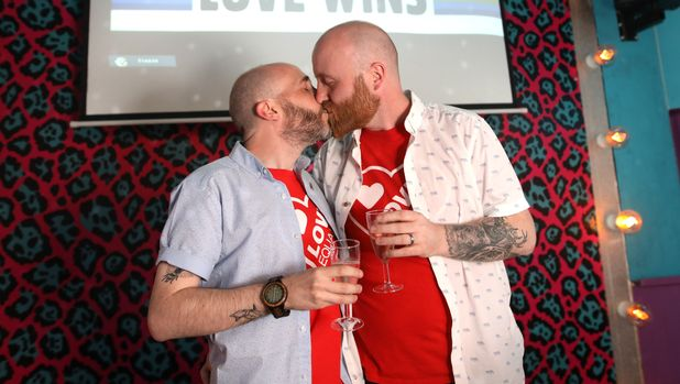 Martin Toland (left), kisses his husband John ODoherty at the Maverick bar, Belfast, as same-sex marriage in Northern Ireland came a step closer after MPs voted to legalise it if a new Stormont Executive is not formed by October. (Photo by Peter Morrison/PA Images via Getty Images)