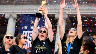 """USA women's soccer player Megan Rapinoe (C) and other team members celebrate with the trophy in front of the City Hall after the ticker tape parade for the women's World Cup champions on July 10, 2019 in New York. - Tens of thousands of fans are poised to pack the streets of New York on Wednesday to salute the World Cup-winning US women's team in a ticker-tape parade. Four years after roaring fans lined the route of Lower Manhattan's fabled """"Canyon of Heroes"""" to cheer the US women winning the 2015 World Cup, the Big Apple is poised for another raucous celebration. (Photo by Johannes EISELE / AFP)        (Photo credit should read JOHANNES EISELE/AFP/Getty Images)"""